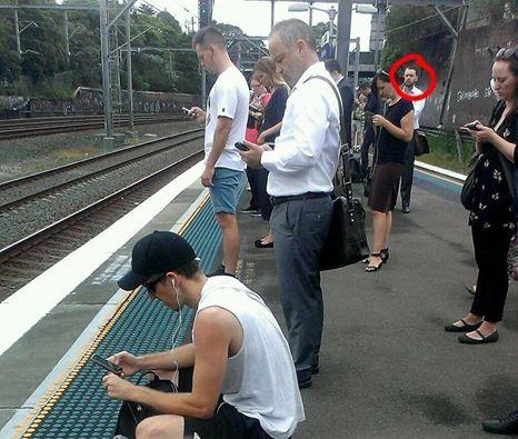 Un homme surpris en train de regarder le monde réel sur le quai d'une gare